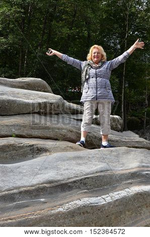 Happy woman rising hands on the picturesque mountains background. Travel concept
