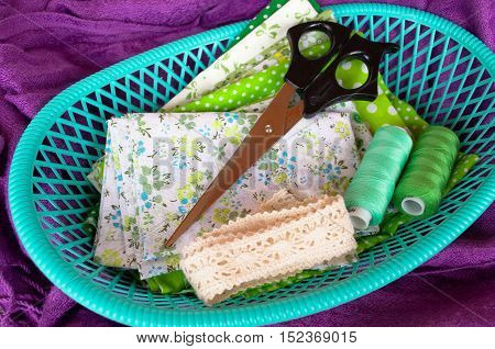 Green fabric, lace, scissors and thread in a green box on purple background