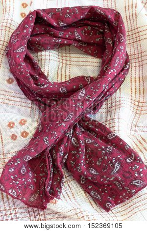 Burgundy scarf on beige background. Women's accessory