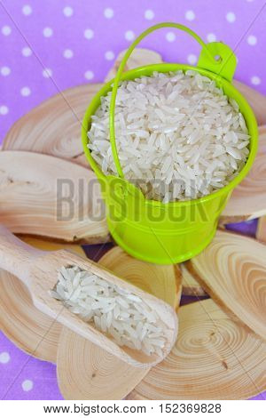 Basmati long grain rice in green metal bucket, a wooden spoon with rice