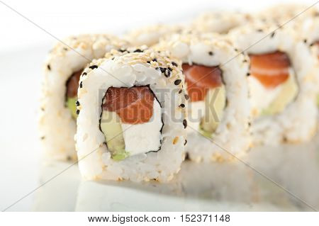 Maki Sushi - Roll with Smoked Salmon, Cream Cheese, Salad Leaf and Avocado inside. Sesame outside.
