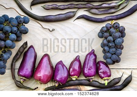 Autumn Food background. Violet bell peppers purple beans blue grapes on a light wooden background. The empty space in the center.