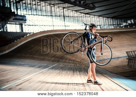 Athlete with a bicycle on velodrome