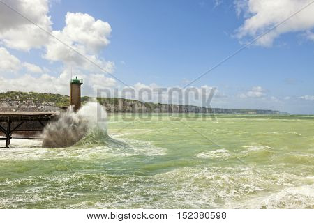 waves crashing against beacon at harbor of Fecamp, cliffs of Alabaster Coast in background