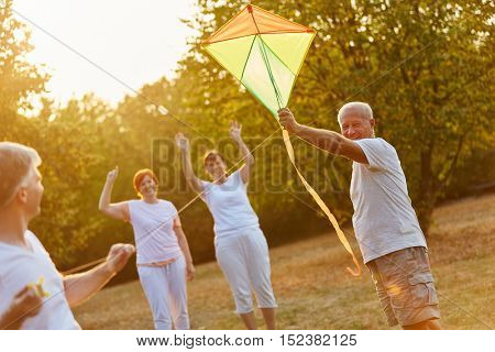 Seniors having fun whith kite flying in the nature in autumn