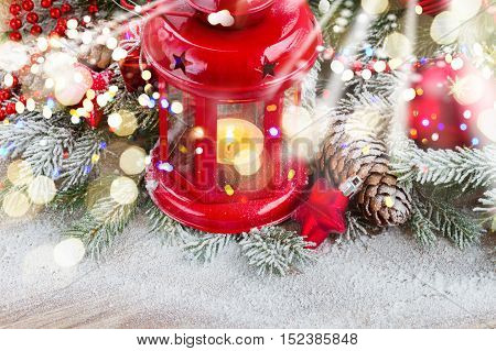 christmas red glowing lantern with decorated evergreen tree and snow on wood with glowing lights