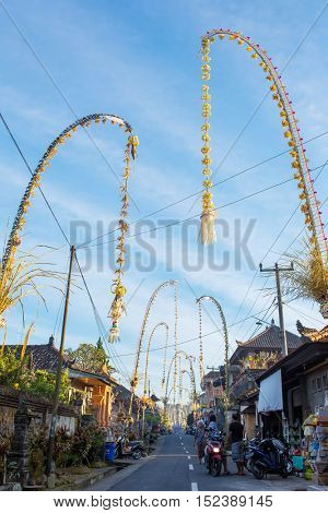 Bali, Indonesia - September 5, 2016: Bali Penjors, decorated bamboo poles along the village street in Bali, Indonesia.