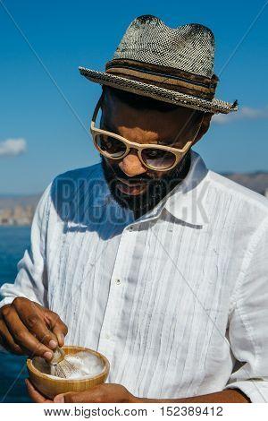 Portrait of elegance bearded man in sunglasses dissolves foam with shaving brush