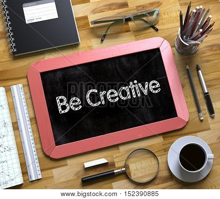 Be Creative - Text on Small Chalkboard.Be Creative - Red Small Chalkboard with Hand Drawn Text and Stationery on Office Desk. Top View. 3d Rendering.