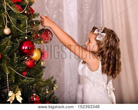 Child decorate on Christmas tree. Little girl getting dressed Christmas ball.