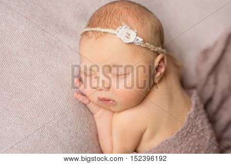 lovely sleeping newborn girl with flower on her headband with hand under her head