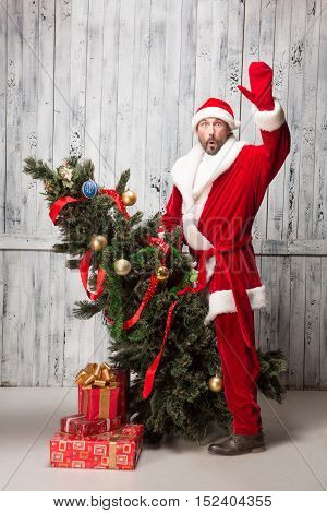 Picture of happy Bad Santa Canta waving to everybody and saying hello while riding on New Year Eve or tree in studio. New Year concept.