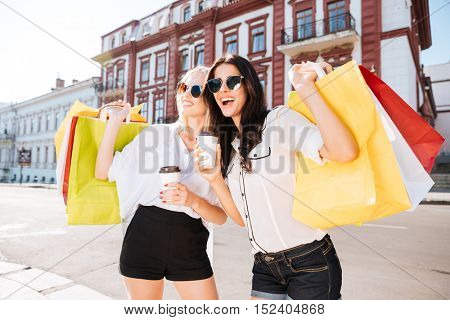 Two happy women holding shopping bags and having fun laughing in street