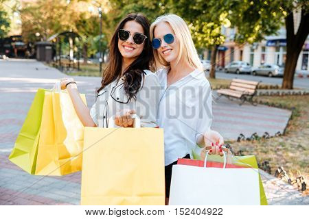Stylish young ladies in sunglasses walking down the street with shopping bags