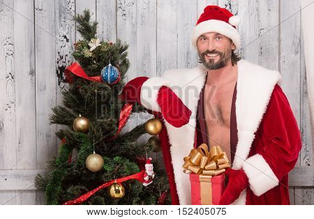 Bad Santa Clause is striptease performer or erotic dancer for New Year or Christmas while posing for photographer in studio.