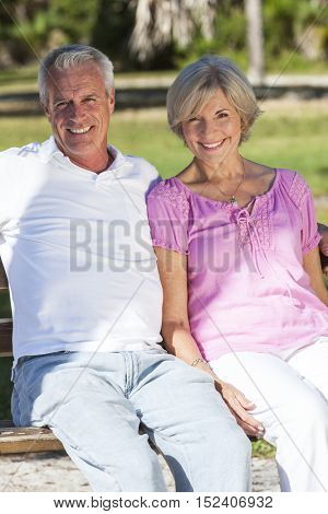 Happy senior man and woman couple sitting together on a park bench outside in sunshine