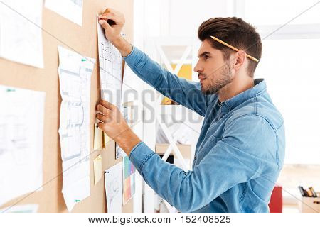 Serius casual businessman posting business plan at the office board while sitting at the desk