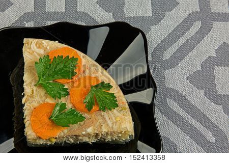 On a gray napkin is black plate with a superimposed portion of jelly chicken. The whole decorated the fresh parsley and sliced carrots. Close flat horizontal view.