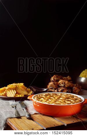 Wooden table served for Thanksgiving dinner. Close view at pumpkin pie. Chips, chicken legs, and mash potatoes on a black background. Vertical shot. Dark photo