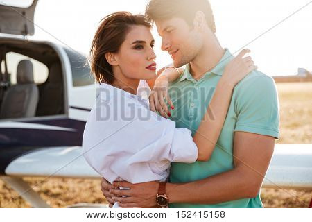 Beautiful young couple standing and hugging near private aircraft