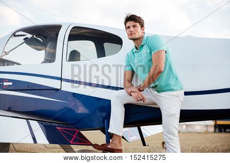 Pensive attrative young man pilot standing near small aircraft