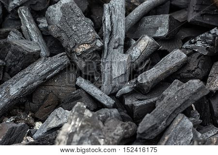 Black charcoal texture background. Natural wood charcoal, traditional charcoal or hard wood charcoal. Pile of charcoal. Details on the surface of charcoal.