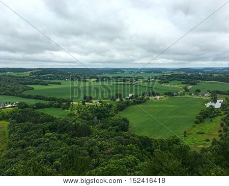 Wisconsin rural landscape with rolling fields hills houses lakes and farms.