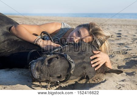 horsewoman and her black stallion laid down on the beach