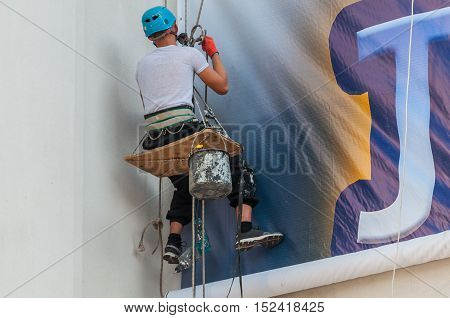 Climbers on a vertical wall mounted billboard.