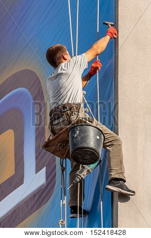Climber on a vertical wall mounted billboard.