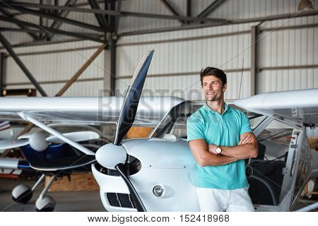 Handsome young man standing with arms crossed and smiling near small plane