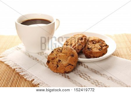 Close-up of round chocolate biscuits and a cup of coffee