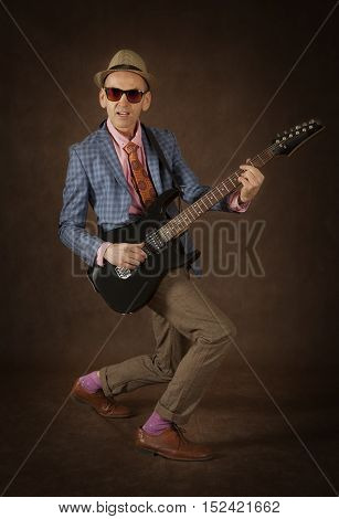 Rockabilly man playing the guitar in front of brown background
