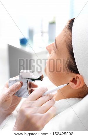 Professional ear piercing. Beautician pierces the ears of the woman in the beauty salon.