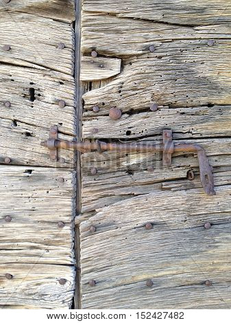 Rusty latch fixed on an old wooden door