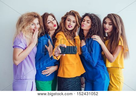 Fashion girls in bright clothes. Beautiful women with professional makeup and crazy hair style, over white background.