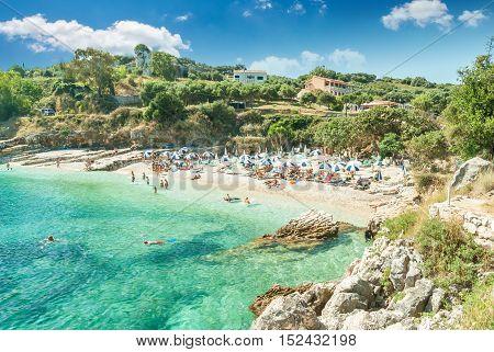 Kassiopi Beach, Corfu Island, Greece. Sunbeds and parasols (sun umbrella) on the beach. Tourists relaxing on beautiful beach of Kasiopi in the north area of Corfu Island.