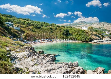 Kassiopi Beach, Corfu Island, Greece. Sunbeds and parasols (sun umbrella) on the beach. Tourists relaxing on beautiful beach of Kasiopi in the north area of Corfu Island.