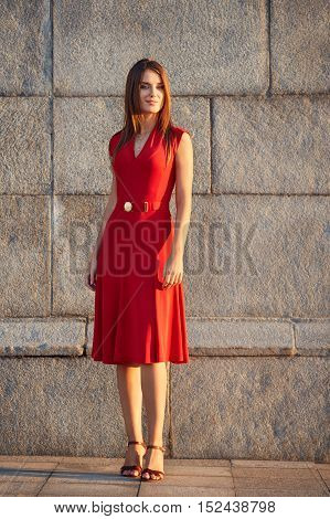 Full Length Portrait Of Attractive Elegant Young Woman In A Red Dress, Standing On The Sidewalk On S
