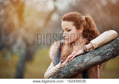 Portrait Of Beautiful Young Woman In Fur In Autumnal Park