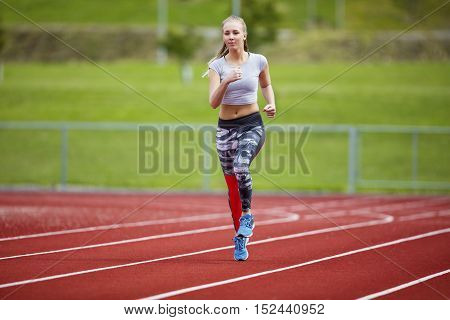 Full length of young woman in sportswear running on sports track