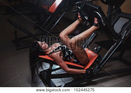 Sportive Woman Using Weights Press Machine For Legs At The Gym. Pretty Brunette Exercising In A Simu