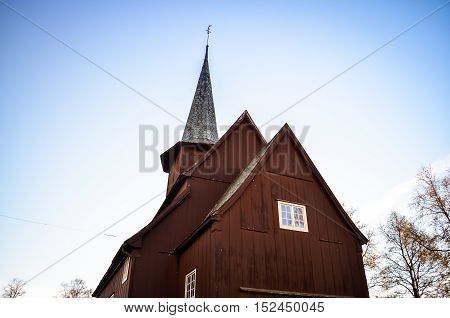traditional red wooden stave church and blue sky in norway
