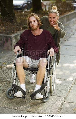 woman pushing wheelchair of young man and showing him something