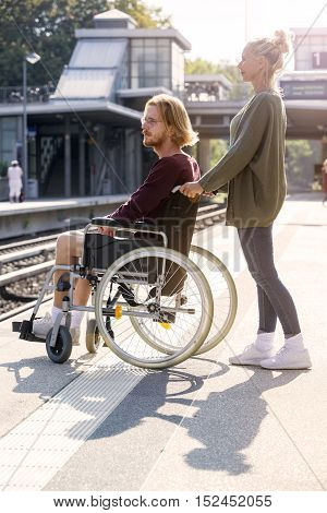 woman pushing a young man in wheelchair at train station