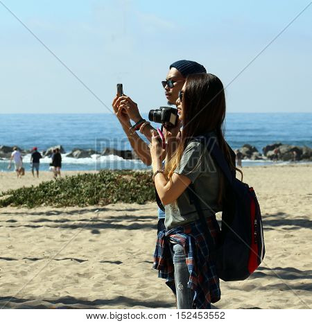 Venice Beach, California, 10/15/16--Hipster young Asian tourist couple snaps photos with cell phone and camera at Venice Beach, California. Many tourists visit Venice Beach.