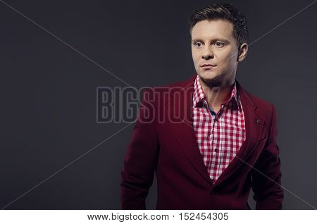 Young businessman looking at camera with discrete smiling and proud expression.