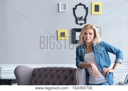 Posing serious blond woman leaning on grey sofa with one arm.