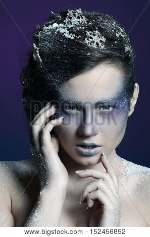 Portrait of a beautiful girl in the frost on his face on a blue  background