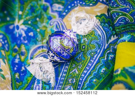 KILCHBERG SWITZERLAND - MAR 20 2014: Tasty blue Lindt Lindor chocolate on a colored silk background Lindt & Sprüngli AG more commonly known as Lindt is a Swiss chocolatier and confectionery company founded in 1845 and known for their chocolate truffle bal